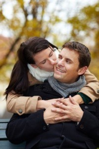 Woman giving man sitting on bench a kiss