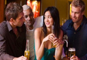 Men chatting up woman in a bar