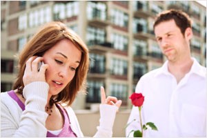 Woman on cell phone ignoring man with rose