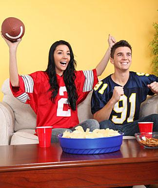 A woman getting into boyfriend's football game