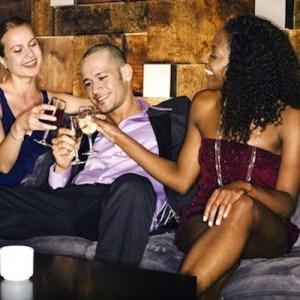 Guy enjoying drinks with two women