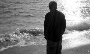 Lonely man walking on along beach