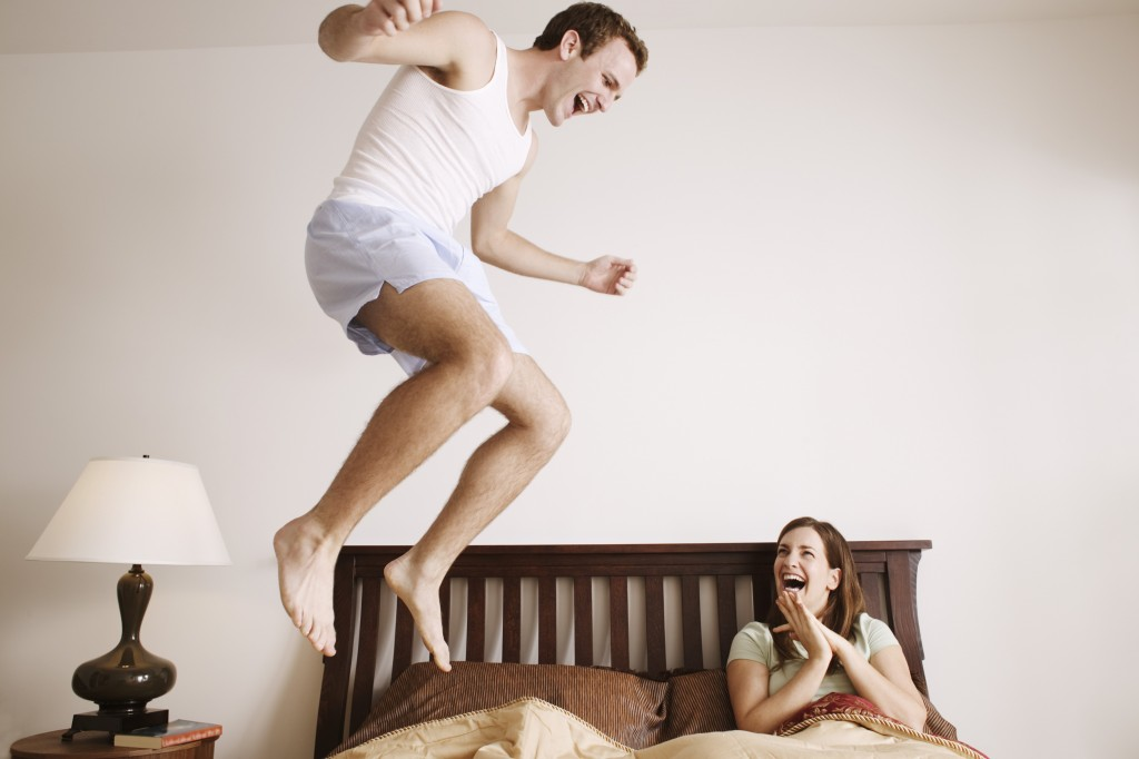 Man jumping on his bed