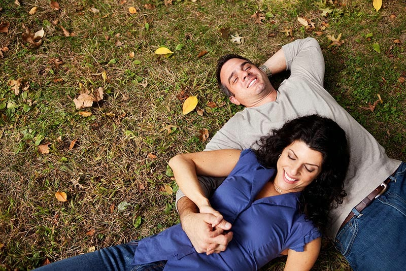 Happy couple snuggling in the grass