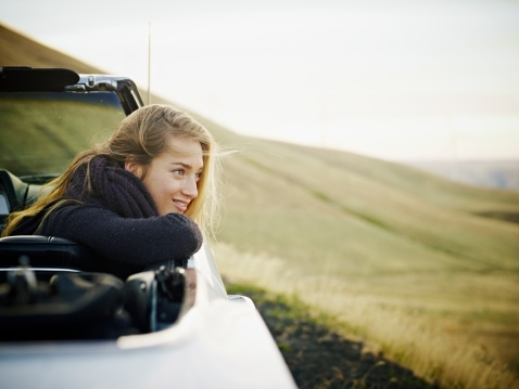 Happy woman in back of convertible