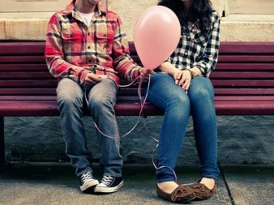Man giving a balloon to a woman