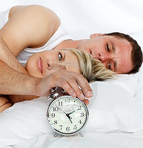 Couple in bed with clock.