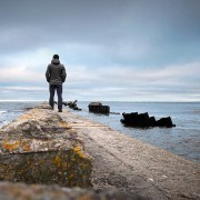 Man standing on pier looking out at ocean