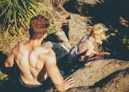 Couple climbing in swim suits.