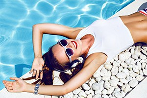 Woman laying poolside smiling.