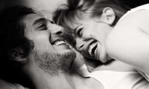 Couple laughing in bed together