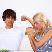 woman holding a man's flexed bisep at that table