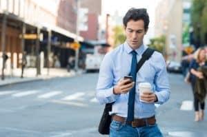 man texting on street